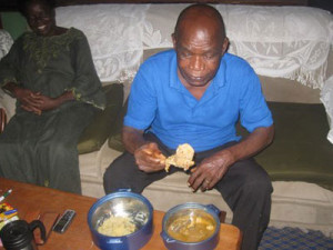 At home - A man enjoying a meal of pounded yam and white soup (ohe sarara) with his family