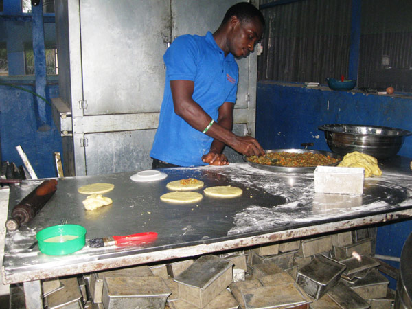 A man preparing meat pie at Ndibe Beach Hotel in Afikpo